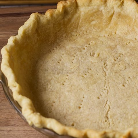 The bottom pie crust in a pie plate, ready to bake.