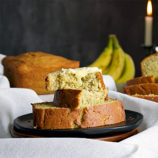 Two pieces of banana bread with butter on a plate.