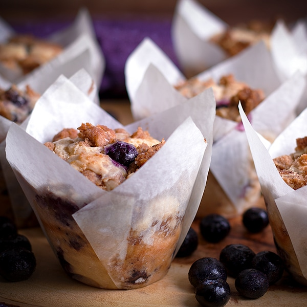 A tray of warm sour cream blueberry muffins with brown sugar streusel.