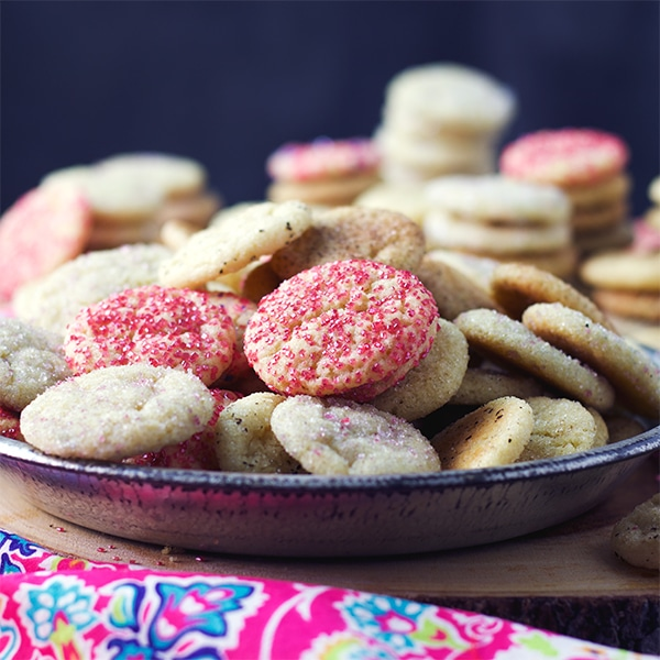 A plate full of buttery sugar cookies rolled in sprinkles.