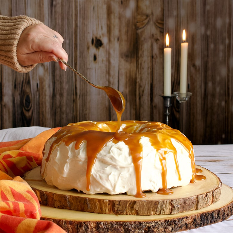 Drizzling Salted Caramel Rum Sauce over Carrot Cake Bundt Cake with Cream Cheese Buttercream.