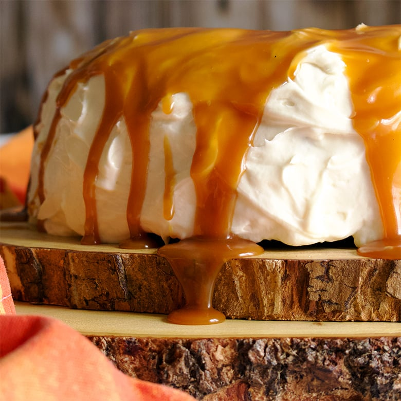 Salted Caramel Rum Sauce dripping down the side of a carrot cake with cream cheese buttercream.