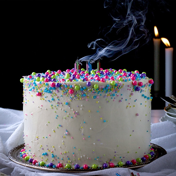 A three layer vanilla cake iced with vanilla buttercream and decorated with sprinkles. Candles in the top of the cake have just been blown out and smoke trails from them.