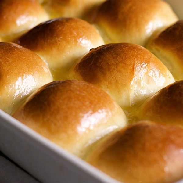 A pan of freshly baked homemade dinner rolls brushed with melted butter.