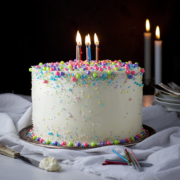 Perfect Vanilla Cake iced with Vanilla Italian Meringue Buttercream, decorated with sprinkles and birthday candles.