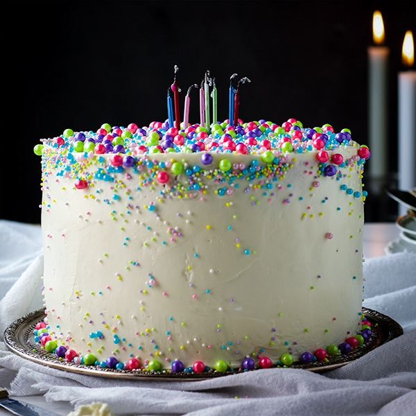 Perfect Vanilla Cake iced with Vanilla Italian Meringue Buttercream, decorated with sprinkles and blown out birthday candles.