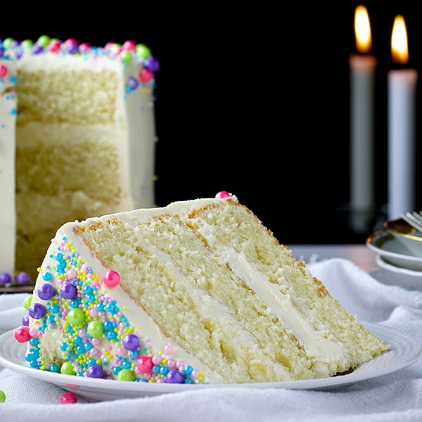 A slice of 3-layer perfect vanilla cake with vanilla Italian Meringue Buttercream