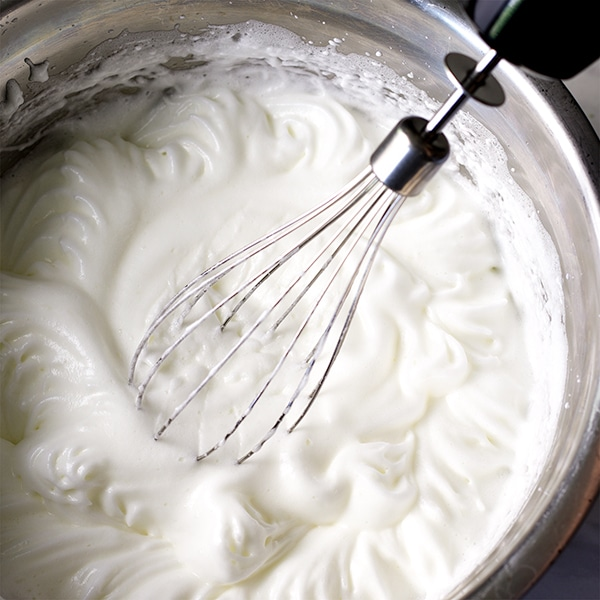 Whipping egg whites before folding them into the batter for vanilla cake.