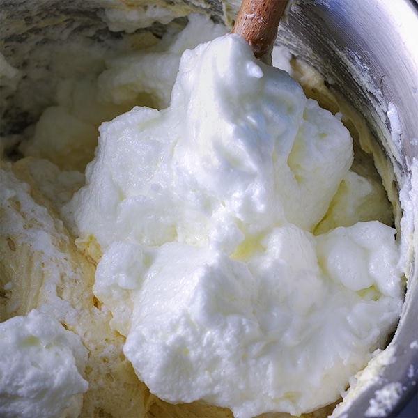 Folding beaten egg whites into the batter of vanilla cake.