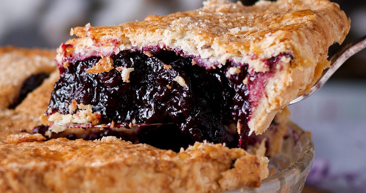 Serving a slice of homemade blueberry pie.