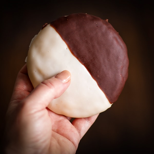 Holding a New York Black and White Cookie.