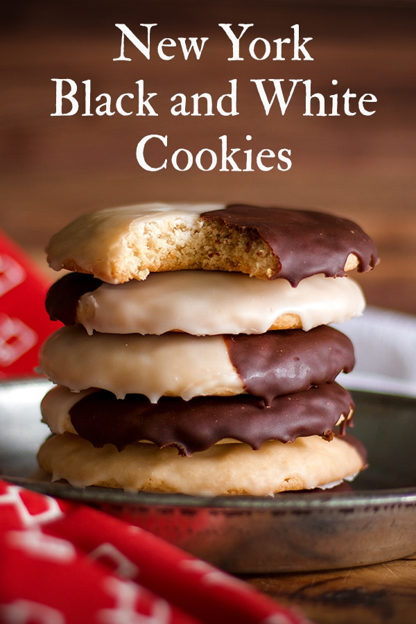 A stack of New York Black and White Cookies, the top cookie has a bite taken out of it.