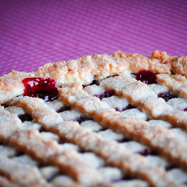 A Triple Cherry Pie, warm from the oven, with cherry filling bubbling out from the edges of the crust.