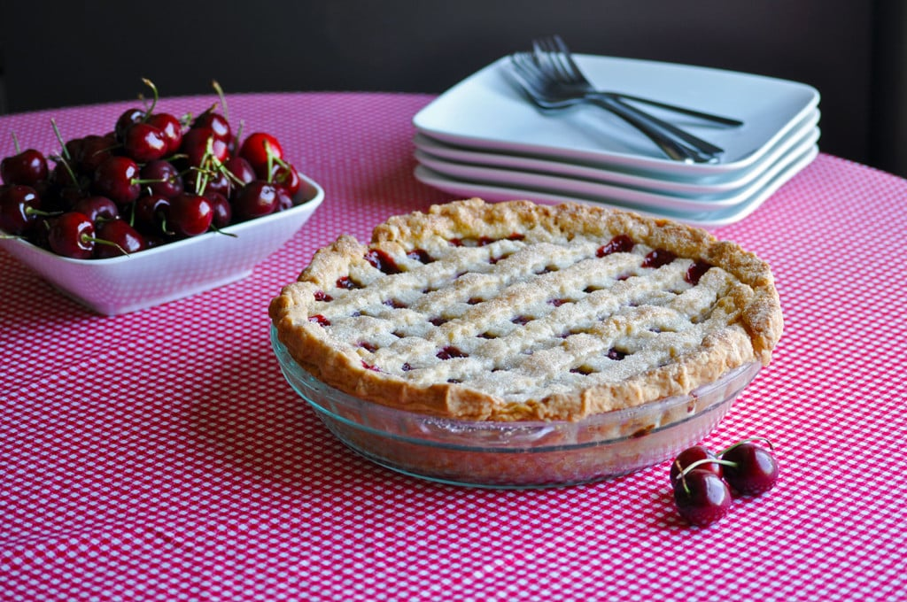 A triple cherry pie with a lattice crust on a checkered table cloth with a bowl of fresh cherries.