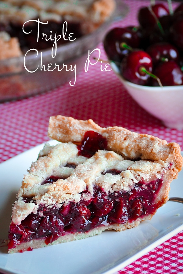 A slice of triple cherry pie on a plate, ready to eat.