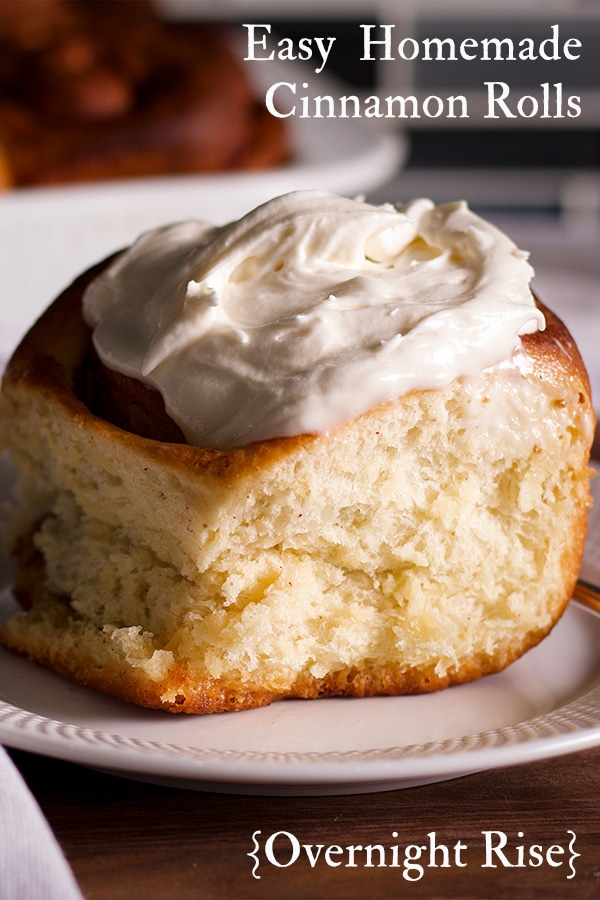 A freshly baked homemade cinnamon roll on a plate, ready to eat.