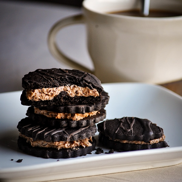 A stack of coffee and cream hazelnut mocha sandwich cookies on a plate.