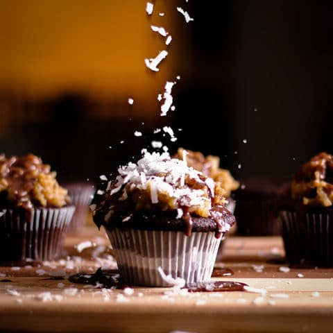 Sprinkling coconut over the top of a German Chocolate Cupcake.