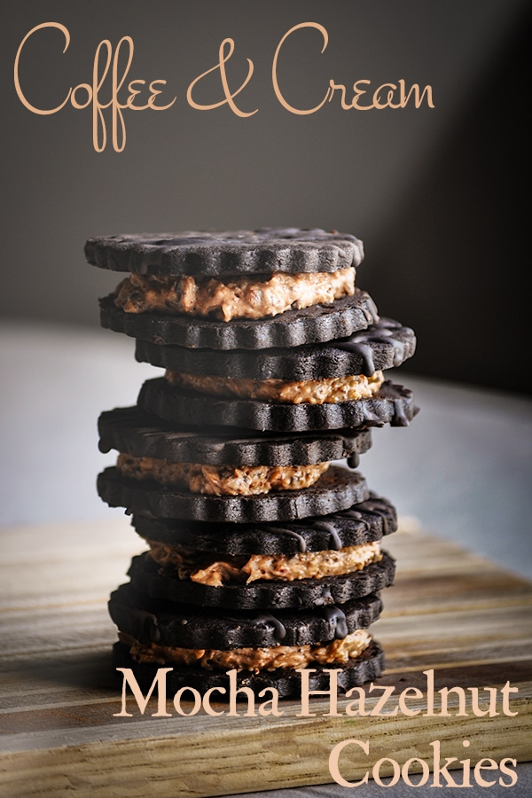 A stack of Hazelnut Mocha Coffee and Cream Sandwich Cookies on a wooden tray.