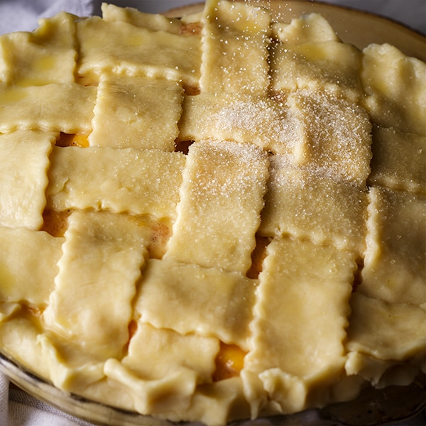 Sprinkling sugar over the top of a peach pie with a lattice crust before baking.