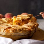 Serving a slice of peach pie with a lattice crust.