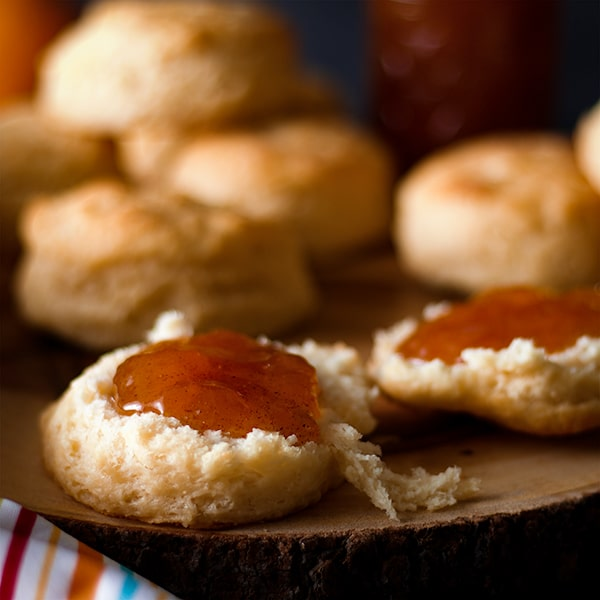 A biscuit that's been split in half and spread with peach jam.