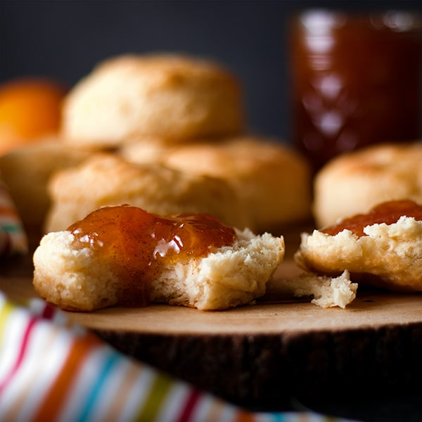 A biscuit that's been split in half and spread with peach jam. One half of the biscuit has a bite taken out of it.