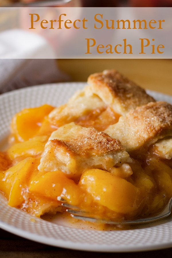 A slice of peach pie with flaky homemade pie crust.