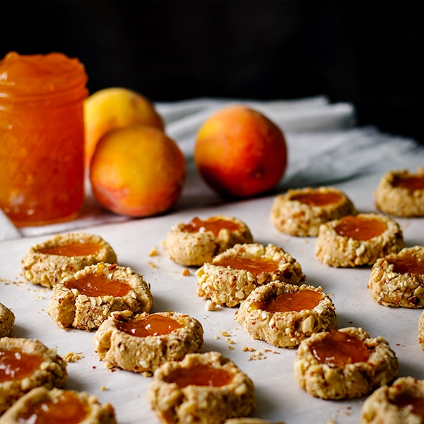 A tray of peach almond thumbprint cookies ready to be baked.