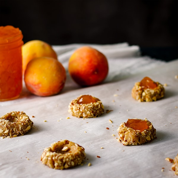 Filling peach almond thumbprint cookies with peach preserves.