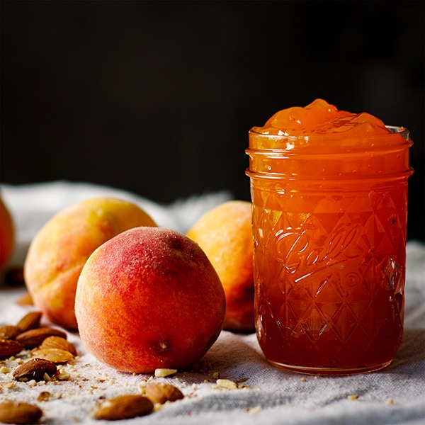 A jar of peach preserves with fresh peaches and roasted almonds.