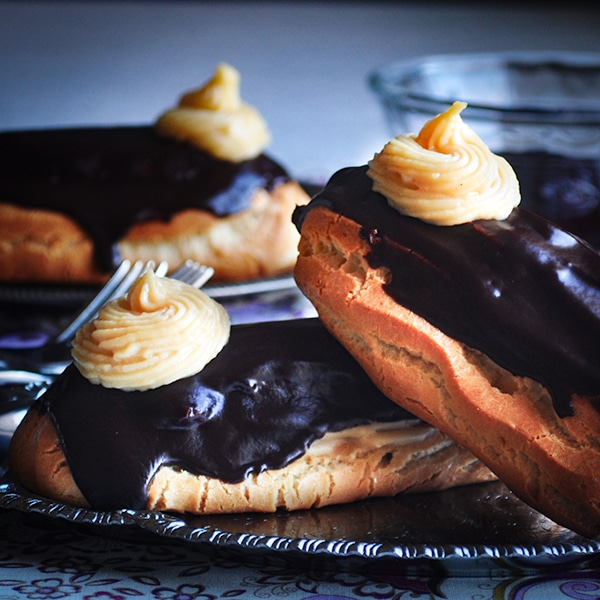 A plate of chocolate eclairs filled with vanilla pastry cream.