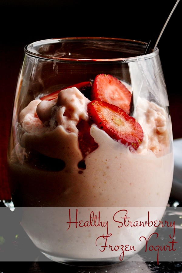 A cup of healthy strawberry frozen yogurt with slices of fresh strawberries.