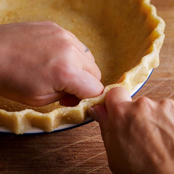 How to pinch the edges of the bottom pie crust for caramel apple pie.