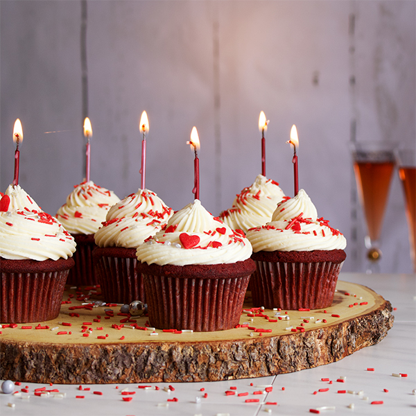 Red velvet cupcakes with cream cheese buttercream with birthday candles.