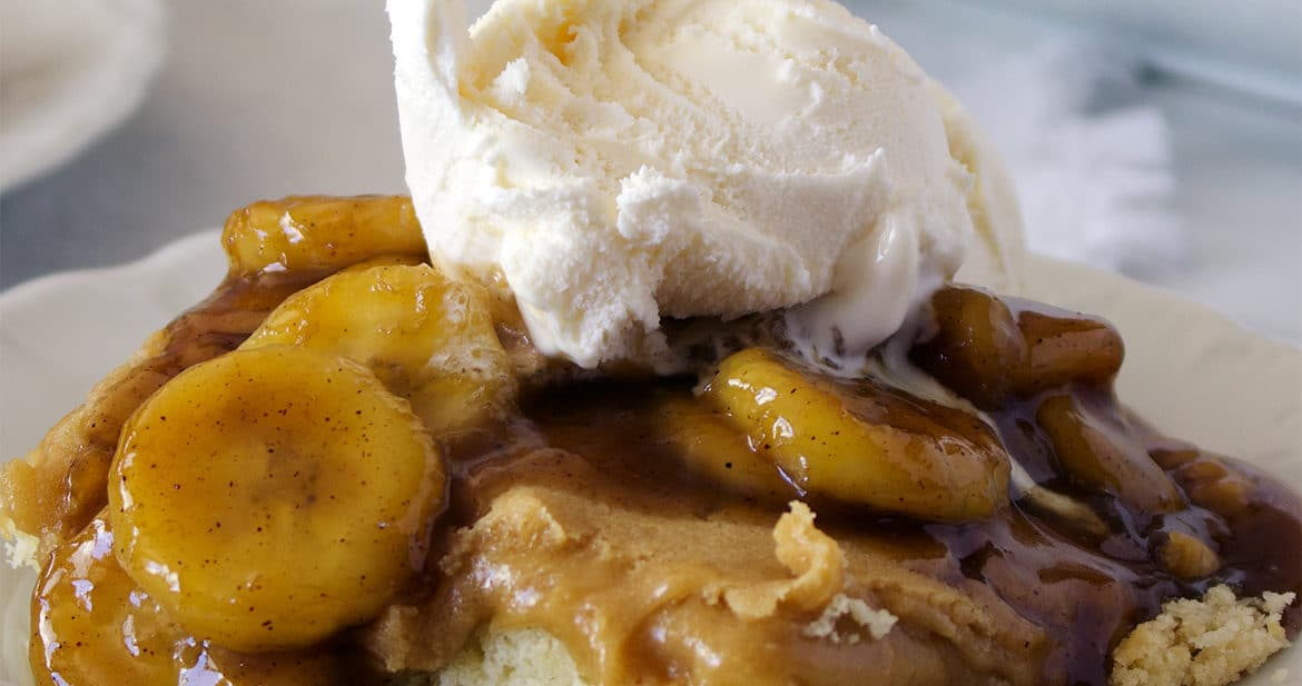 A plate of Bananas Foster Butter Cake with vanilla ice cream. {St. Louis Gooey Butter Cake with Bananas Foster Sauce}