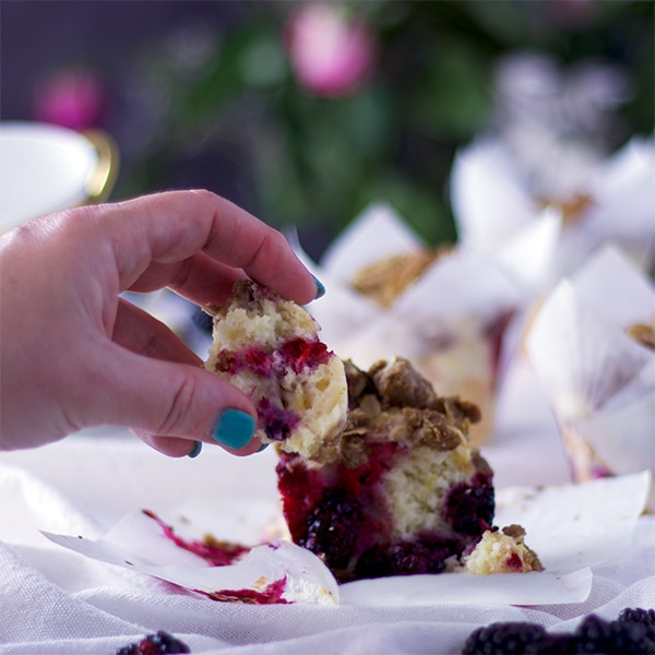 Breaking off a piece of a Mixed Berry Muffin with Brown Sugar Streusel.
