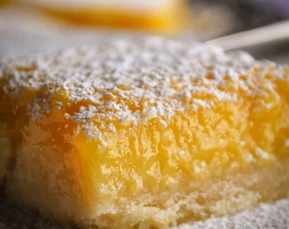 Lemon bars on a serving platter, sprinkled with powdered sugar.