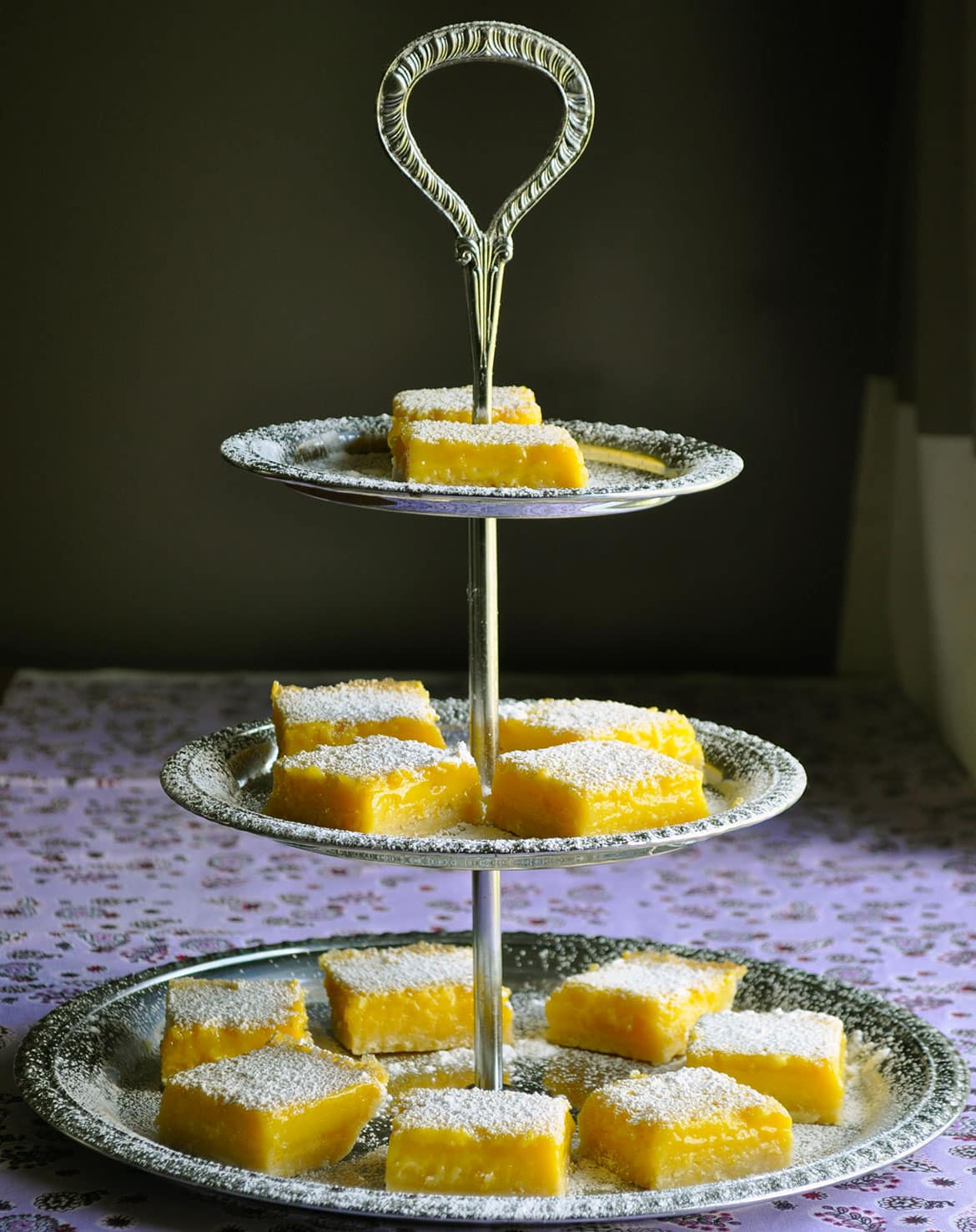 A three tiered dessert tray holding lemon bars.