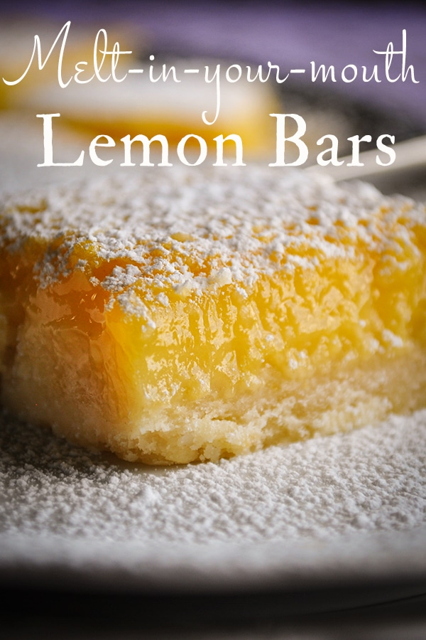 Lemon bars on a serving platter, sprinkled with powdered sugar.