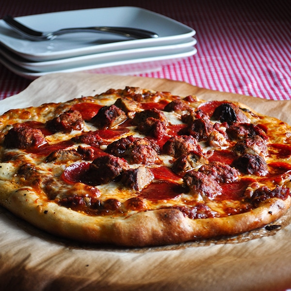 A homemade pizza with pepperoni and sausage.