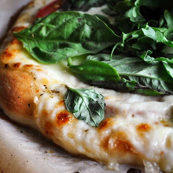 A close up photo of a pizza made with homemade pizza dough to see the golden crust and melted cheese.