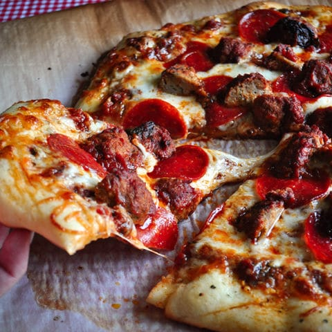 Someone taking a slice of pizza made with homemade pizza dough, pepperoni and sausage.