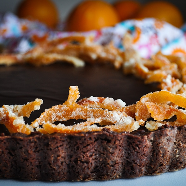A chocolate orange truffle tart on a serving tray, decorated with candied orange peel.
