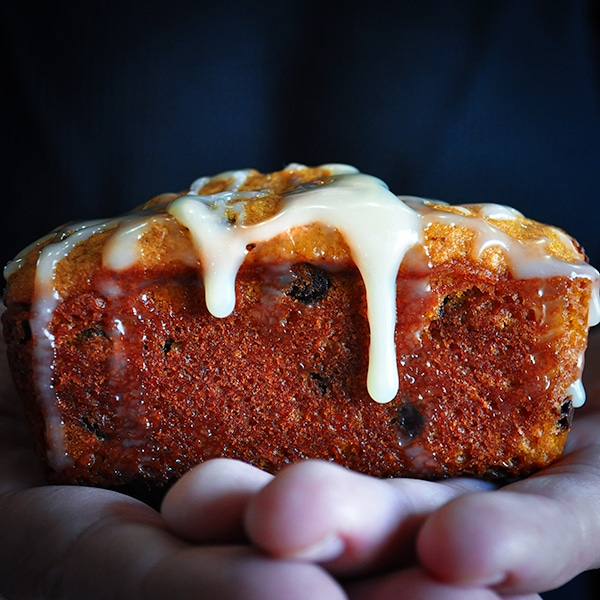Holding a Mini Chocolate Chip Pumpkin Loaf with White Chocolate Ganache.