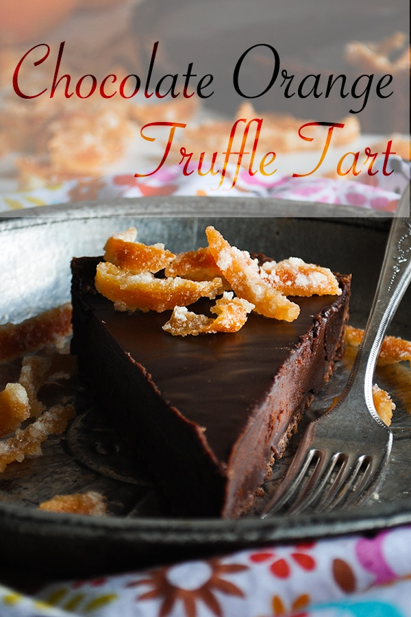 A slice of chocolate orange truffle tart on a plate with a fork.
