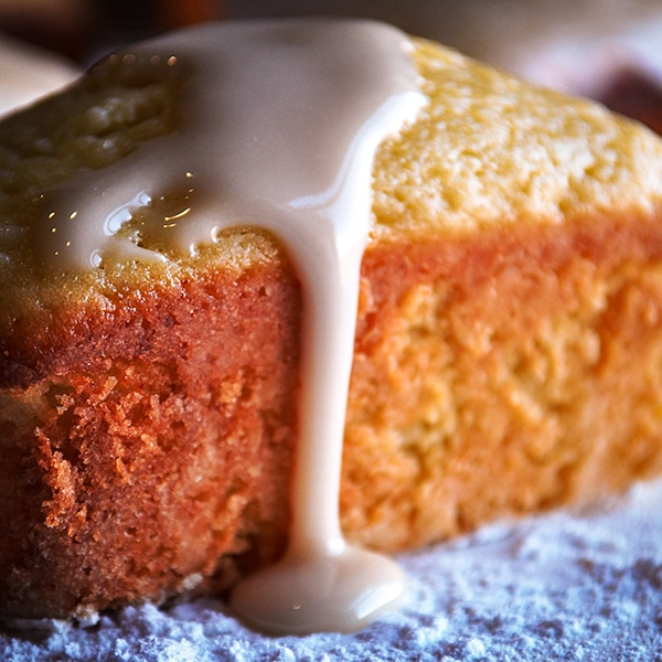 Lemon glaze dripping from the side of a mini Lemon Ricotta Olive Oil Loaf.