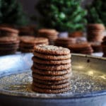 A stack of small chewy ginger snap cookies on a plate.