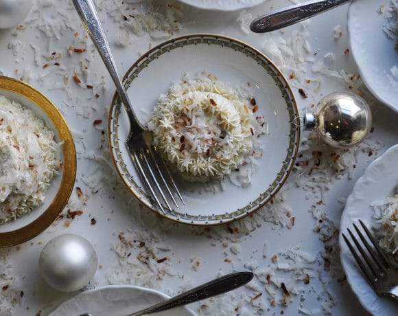 Several plates of mini coconut cakes with maple Italian meringue buttercream.