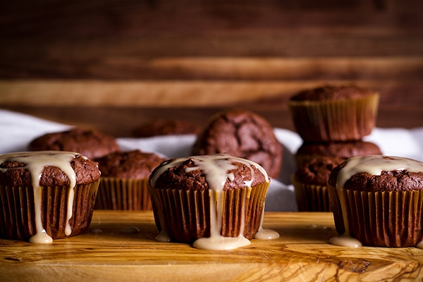 A tray of chocolate muffins with vanilla glaze dripping down their sides,